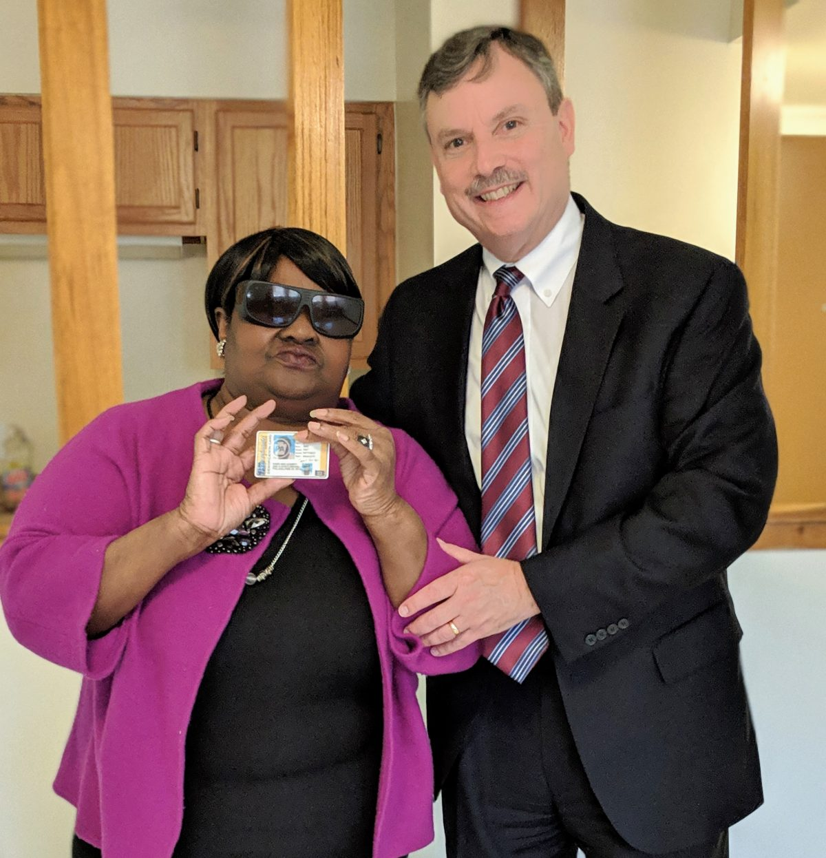 Client, with her volunteer attorney, holding her new photo ID.